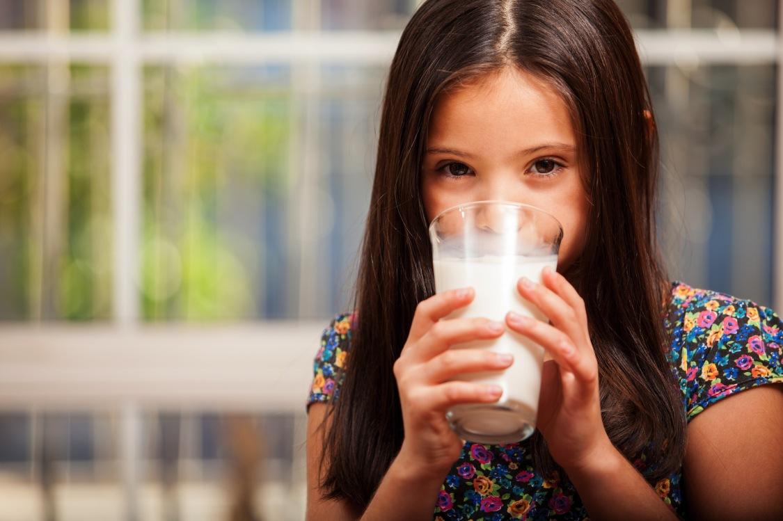 dziewczynka pijąca mleko z szklanki